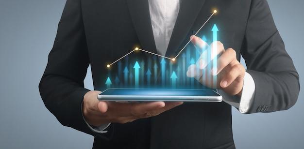 Plano de empresário gráfico de crescimento e aumento do tablet de indicadores positivos de gráfico na mão