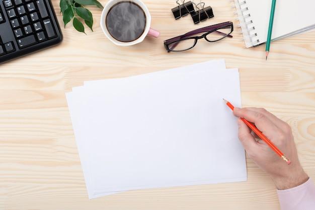 Plano de espaço de trabalho de escritório em casa com teclado, papel em branco, caderno e acessórios.