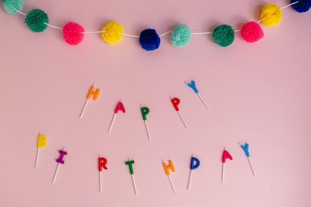 Plano de feliz aniversário soletrado com velas de bolo coloridas e guirlanda de pompon em um fundo rosa com espaço de cópia. maquete de celebração.
