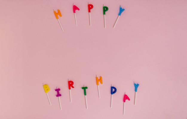Plano de feliz aniversário soletrado com velas de bolo coloridas em um fundo rosa com espaço de cópia. maquete de celebração.