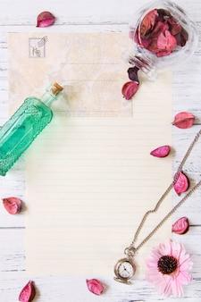 Plano de fotografia stock de pétalas de flores roxas carta envelope papel vidro transparente garrafa relógio de bolso