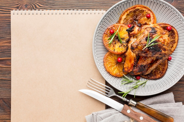 Plano de frango assado e fatias de laranja no prato com talheres e bloco de notas em branco