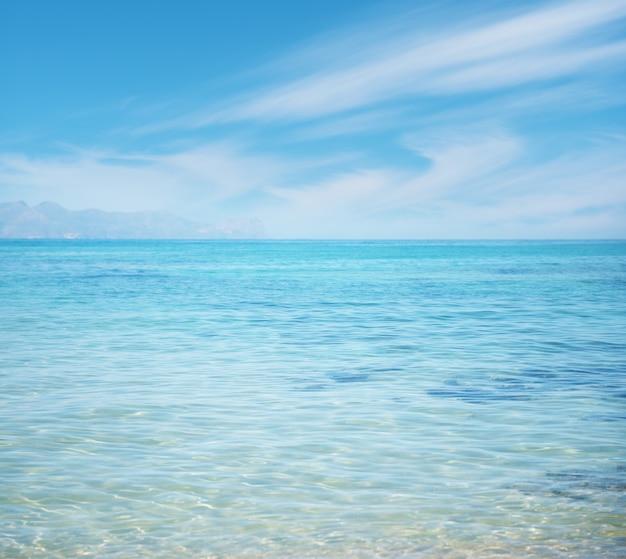 Plano de fundo com mar limpo e céu ensolarado