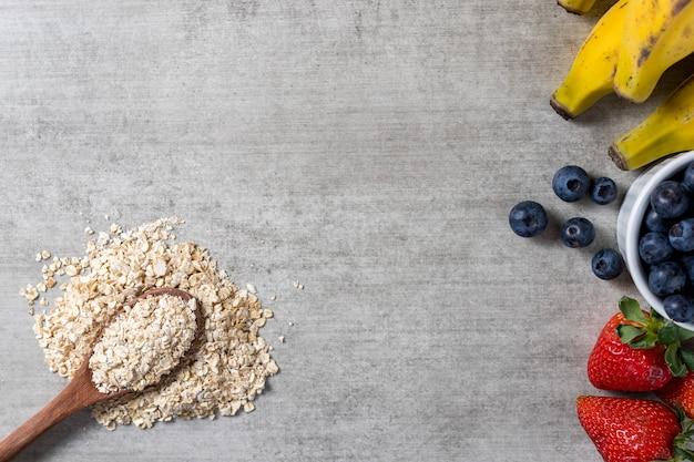 Plano de fundo com uma colher cheia de aveia e algumas frutas frescas saudáveis em uma mesa de madeira. bananas, mirtilos e morangos. vista do topo. copie o espaço.