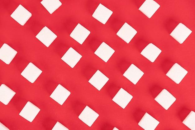 Plano de fundo, cubos de açúcar em um fundo vermelho.