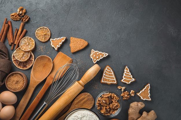 Plano de fundo culinário festivo ingredientes biscoitos de gengibre e utensílios de cozinha em um fundo marrom