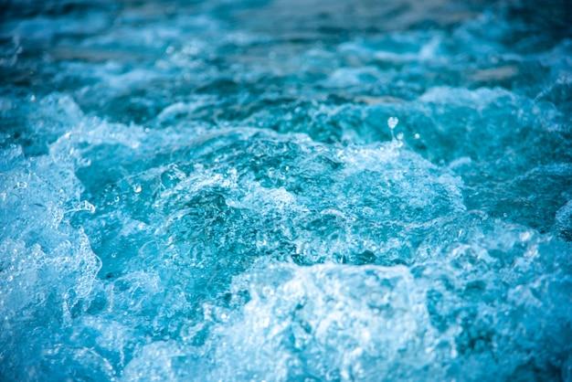 Plano de fundo da superfície da onda de respingos de água atrás da lancha a motor em movimento rápido