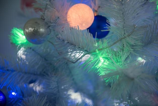 Plano de fundo de ano novo - árvore de natal decorada com guirlandas, close-up.
