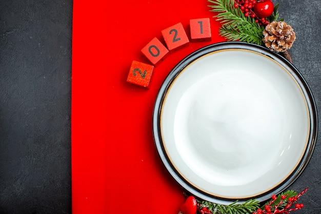 Plano de fundo de ano novo com acessórios de decoração de prato de jantar ramos de abeto e números em um guardanapo vermelho em uma vista horizontal de mesa preta