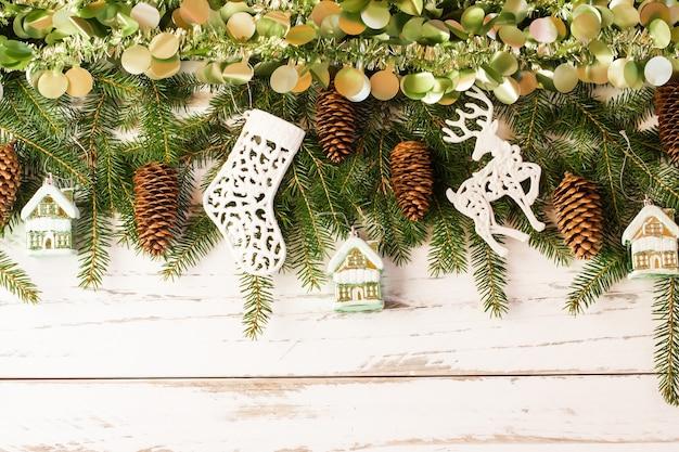 Plano de fundo de ano novo de natal com uma grande guirlanda de enfeites em uma mesa de madeira branca. vista do topo.