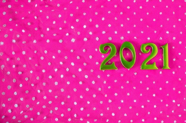 Plano de fundo de ano novo. números verdes sobre fundo rosa com pontos brancos. festivo