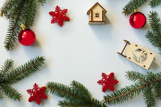 Plano de fundo de ano novo ou natal com ramos de abeto, bolas vermelhas e flocos de neve. brinquedos de madeira. layout plano. vista do topo. fundo branco.