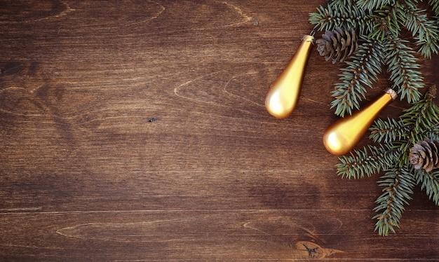 Plano de fundo de ano novo. ramos de abeto em uma mesa de madeira. ornamentos para a árvore do ano novo. conceito de natal