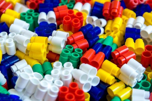 Plano de fundo de blocos de construção de detalhes coloridos de plástico peças de pequenas peças sobressalentes brilhantes para brinquedos