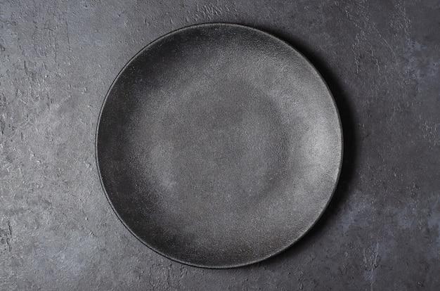 Plano de fundo de concreto texturizado cinza escuro para design com prato preto de comida. copie o espaço.