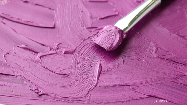 Plano de fundo de cor de óleo roxo e pincel de pintura close-up