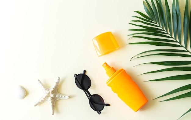 Plano de fundo de férias de verão com protetor solar, folha de palmeira e vista superior de acessórios