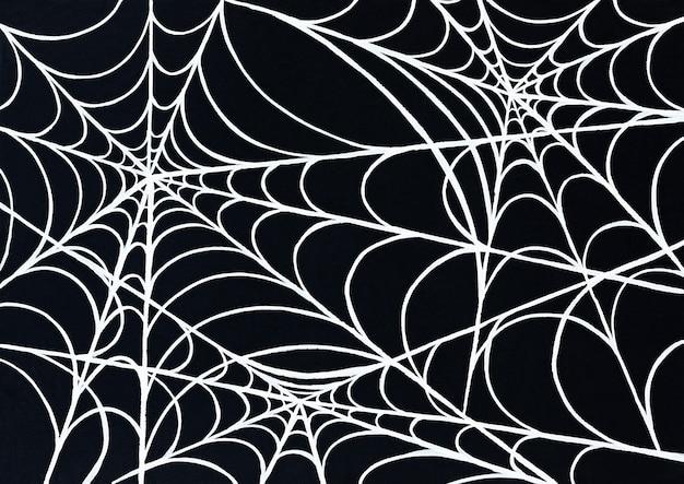 Plano de fundo de halloween de teia de aranha branca em uma superfície preta