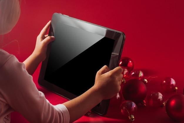 Plano de fundo de natal contra o qual a criança segura um tablet nas mãos