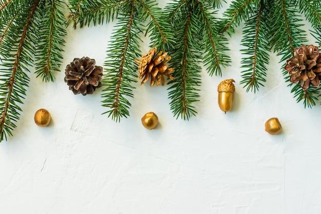 Plano de fundo de natal ou ano novo com elementos decorativos feitos por mãos de soja. cones dourados, nozes, bolotas. uma cópia do espaço.