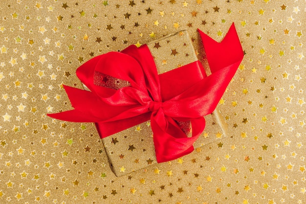 Plano de fundo de natal ou festa com caixa de presente de ouro com laço vermelho em dourado