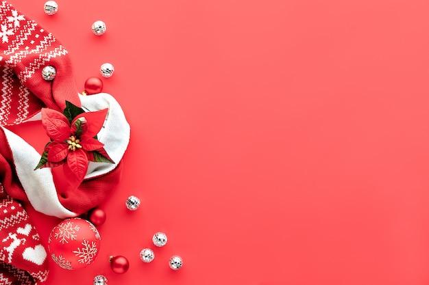Plano de fundo de natal, plana leigos com decorações brancas e vermelhas em fundo vermelho coral, espaço de texto. cachecol, bolas de discoteca e uma grande bugiganga ornamentada.
