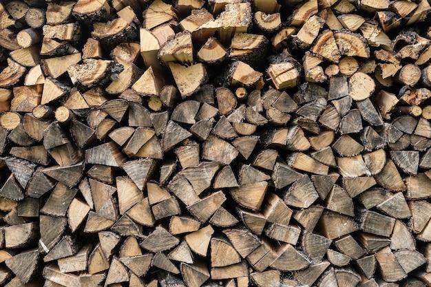 Plano de fundo de toras de madeira lisas cortadas. corte a textura de madeira. pilha de lenha picada preparada para o inverno