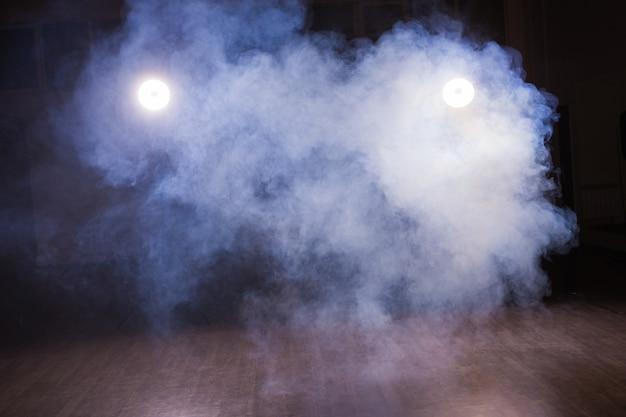 Plano de fundo de uma sala vazia com fumaça e luz. fundo abstrato azul escuro na aula de dança.