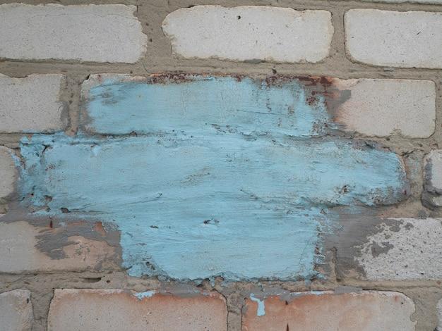 Plano de fundo de uma velha parede de blocos brancos com um lugar de cor azul para o seu texto. copie o espaço