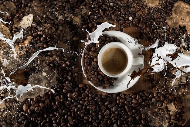 Plano de fundo de uma xícara de café em grão com respingo de leite nas tábuas de madeira