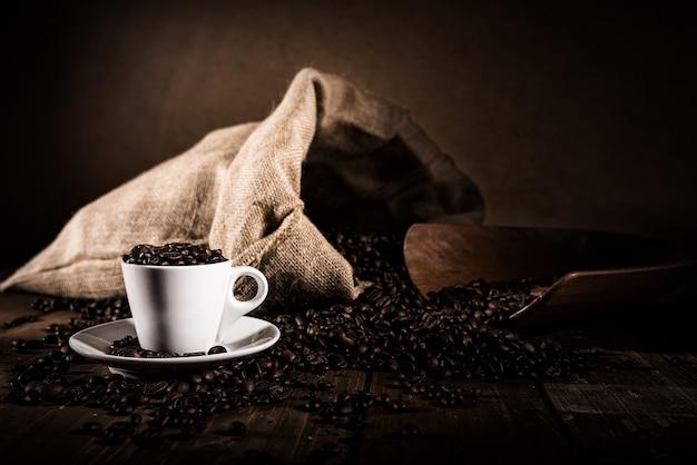 Plano de fundo de uma xícara de café em grão com saco de juta e fiador