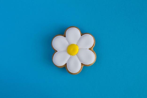 Plano de fundo de verão criativo. camomila em forma de pão de mel no fundo azul. vista superior. espaço de cópia.