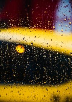 Plano de fundo desfocado da rua de nova york com gotas de água, luzes e carros na noite de chuva