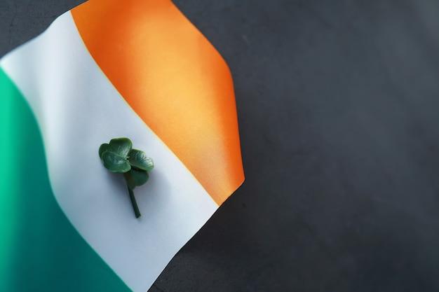Plano de fundo dia de são patrício com bandeira da irlanda. feriado religioso cristão. símbolo do trevo de quatro folhas de boa sorte.