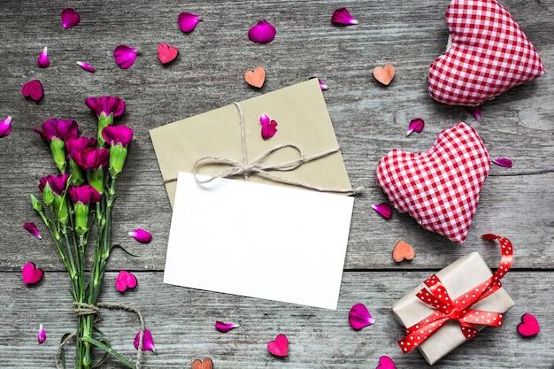 Plano de fundo dia dos namorados. cartão branco em branco com flores de cravo
