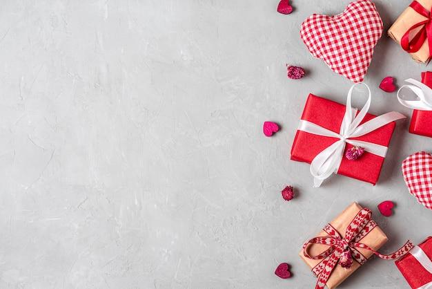 Plano de fundo dia dos namorados com caixas de presente, corações de tecido e flores secas em fundo cinza de concreto. colocação plana. vista de cima com espaço de cópia