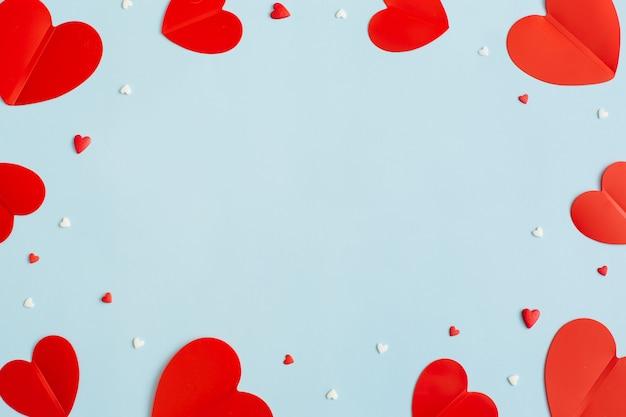 Plano de fundo dia dos namorados com corações vermelhos de papel em fundo azul pastel. camada plana, vista superior, espaço de cópia.