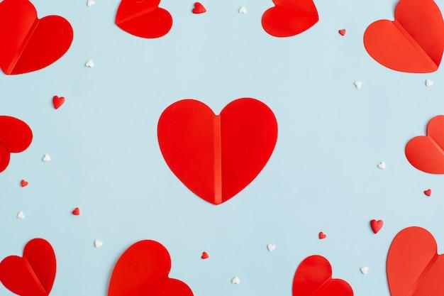 Plano de fundo dia dos namorados com corações vermelhos de papel em fundo azul pastel. camada plana, vista superior.
