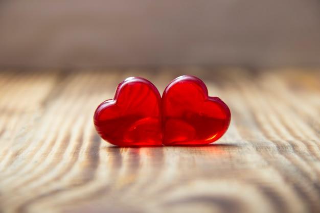 Plano de fundo dia dos namorados com dois corações vermelhos em fundo de madeira