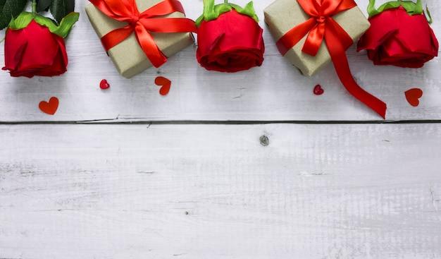 Plano de fundo dia dos namorados com rosa vermelha, corações e caixas de presente na mesa de madeira branca com copyspace para texto.