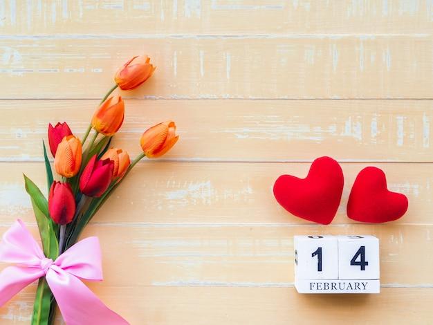 Plano de fundo dia dos namorados. coração vermelho, calendário de madeira do 14 de fevereiro, flor no fundo de madeira.