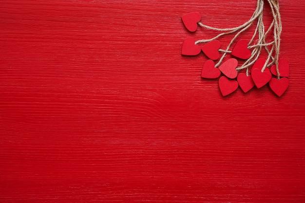 Plano de fundo dia dos namorados. corações de madeira vermelhos no fundo vermelho.
