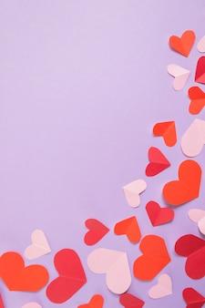 Plano de fundo dia dos namorados. corações rosa e vermelhos em um fundo roxo pastel.