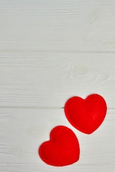 Plano de fundo dia dos namorados. dois corações vermelhos feitos de feltro sobre fundo claro de madeira com espaço de cópia. feliz dia dos namorados.