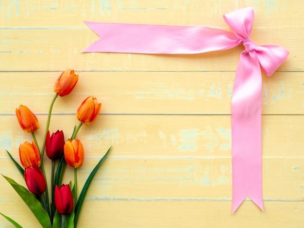 Plano de fundo dia dos namorados. fita e flor cor-de-rosa no fundo de madeira.