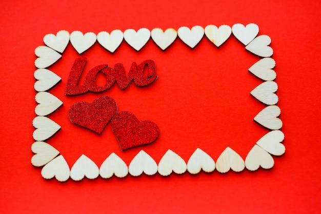Plano de fundo dia dos namorados. os corações de madeira são alinhados com um retângulo sobre um fundo vermelho, com lugar para texto com corações. corações para cartões postais.