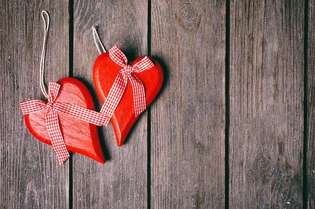 Plano de fundo dia dos namorados. par de corações vermelhos com fita quadriculada em fundo de madeira. vista do topo