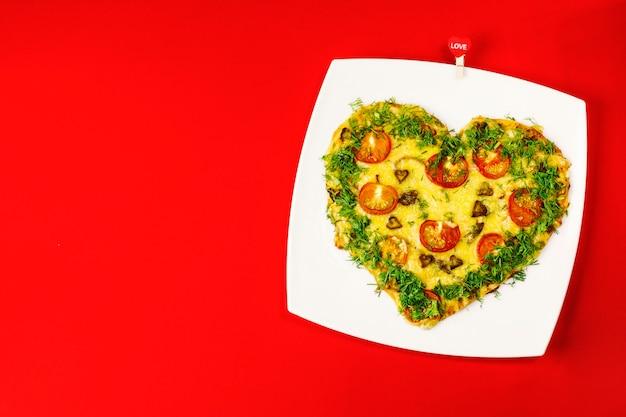 Plano de fundo dia dos namorados. pizza em forma de coração, em um prato branco, sobre um fundo vermelho