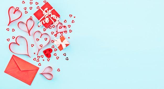Plano de fundo dia dos namorados. presentes de caixa vermelha, confete, envelope vermelho sobre fundo azul pastel. conceito de dia dos namorados. camada plana, vista superior, cópia espaço, banner
