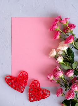 Plano de fundo dia dos namorados. rosas em fundo rosa pastel e um coração vermelho. dia dos namorados . vista plana leiga, superior, cópia espaço.